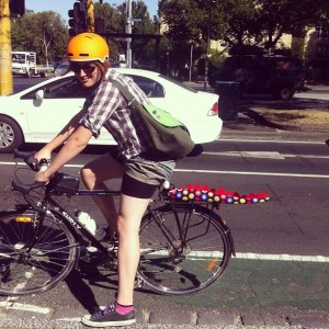 danni on a bike; she is at a stop at an intersection, and her bike is located in the bike lane.