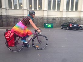 stephanie in a rainbow skirt riding a bike on a road with a building in the background