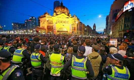 Police look on as protesters stage a sit down protest outside of Flinders Street Station. Photograph: Scott Barbour/Getty Images