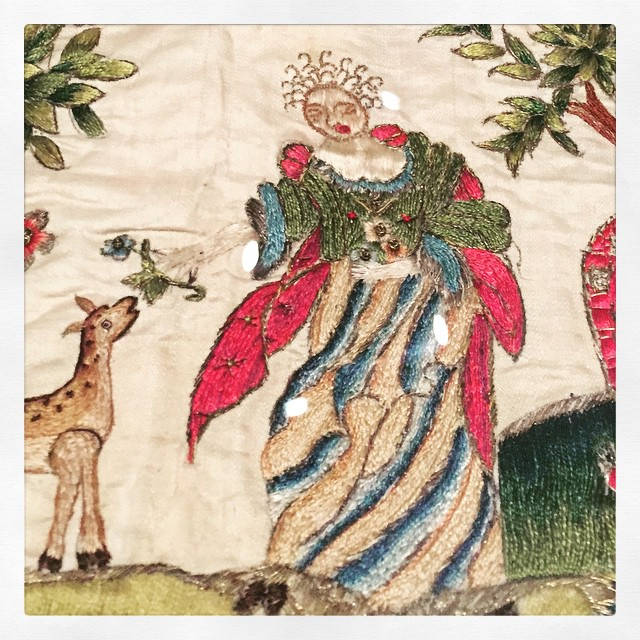 embroidery of a lady with excellent hair feeding some sort of four legged creature