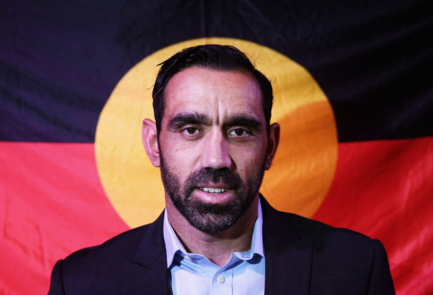 Adam Goodes standing in front of the Mabo flag
