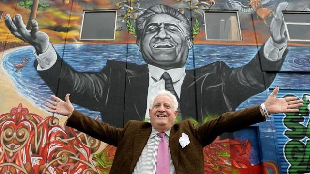 franco cozzo standing with his arms spread in front of a mural of franco cozzo
