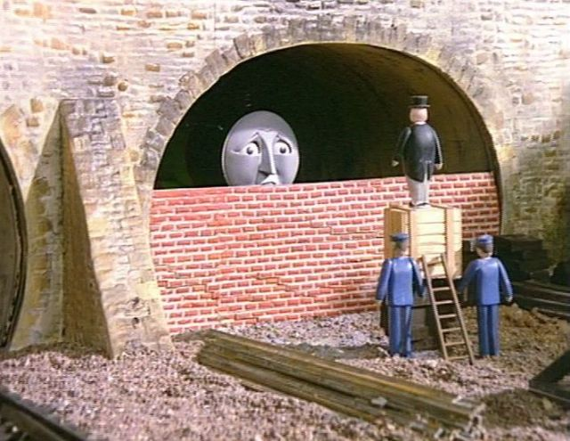 Henry is inside a tunnel. The tunnel is mostly bricked up, with the Fat Controller talking to him.