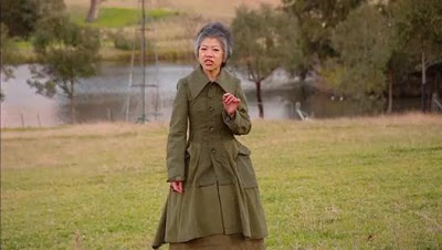 LLC in an amazing green coat with puffy peplum, standing in a field