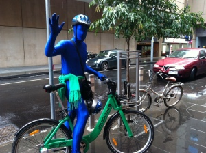 A man in a full lycra bodysuit, face also covered in blue lyrcra, waves from a green share bike.