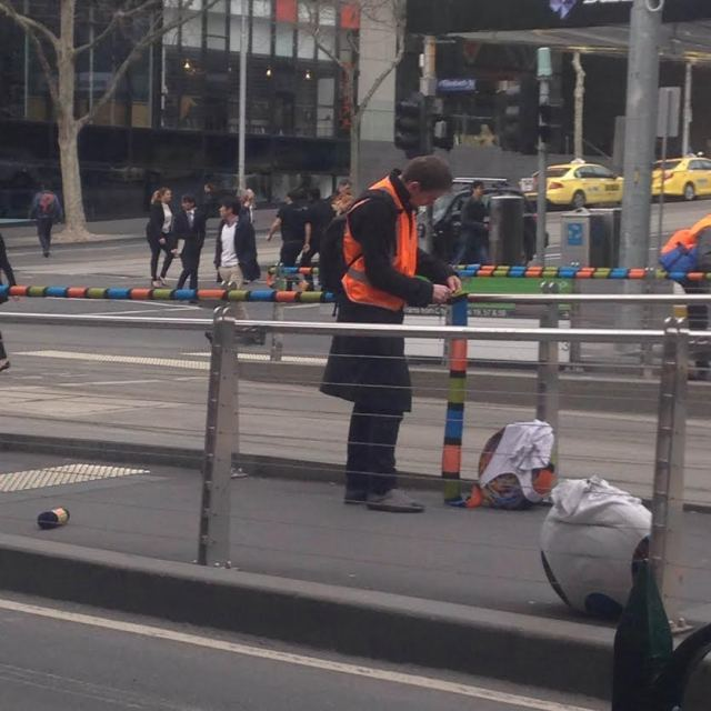 A guy in a hi-vis vest attaches some yarn to a trailing at a tram stop.