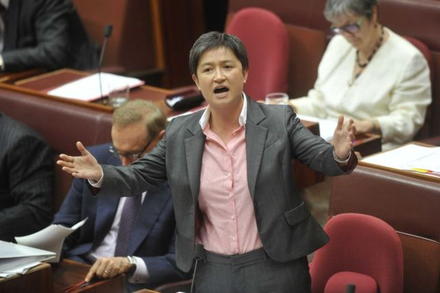 Image: Once again, Penny Wong stands at the microphone, hands out, a look of outrage, confusion and disbelief on her face.