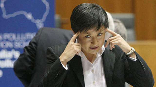 Picture of Wong with her fingers against her temples, a look of forebearance and anger on her face.