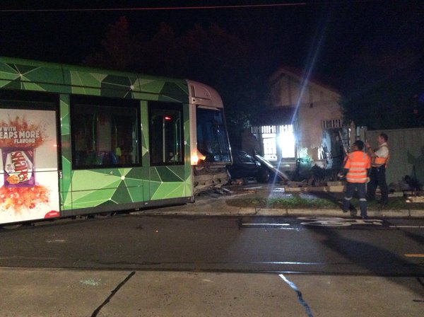 Photo of a battered-looking tram whose front is sitting in a driveway. Behind it is a damaged house.