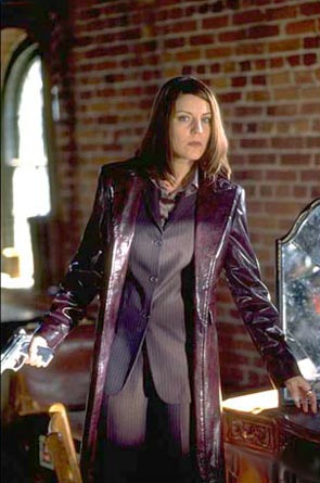 brown haired lady in a suit with a long leather jacket and a gun, looking wary