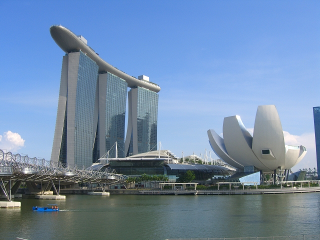 A giant ship sits on top of three sky scrapers, adjacent to a river and a giant building shaped like a half-plucked flower