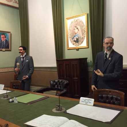 Two mannequins in an old-fashioned office. Both wear suits, one has a goatee, the other an impressive handlebar moustache. A portrait of Queen Victoria sits on the wall behind them, but off to the side is a contemporary portrait.