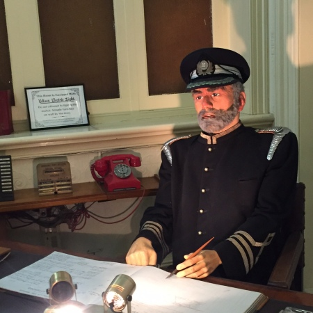 A mannequin in a fireman's uniform sits at a desk, a look of existential despair mingled with resignation on its face. In his hand is a rusted dip pen.