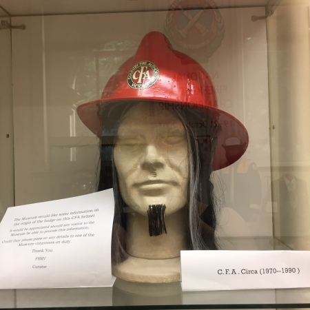 A mannequin's head models a fireman's hat. The face is detailed but unpainted. He wears a long, greying wig, and a small beard that looks like it has been sticky-taped to his face.