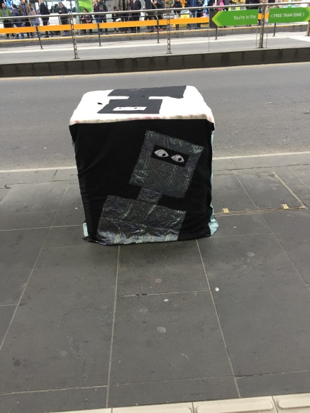 A bollard covered with a fitted quilt depicting Ned Kelly. The top surface has a black Kelly on a white background; the front-facing side has a silver Kelly on a black background with applique eyes.